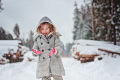 Happy child girl plays in winter snowy forest with tree felling on background. Adorable happy child girl in grey coat plays in winter snowy forest with tree stock images