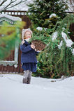 Happy child girl plays in winter snowy garden. With basket of fir branches Stock Photos