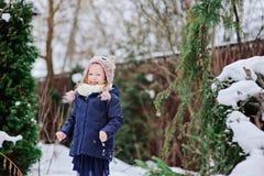 Happy child girl plays in winter snowy garden. Happy child girl in knitted hat plays in winter snowy garden Royalty Free Stock Images