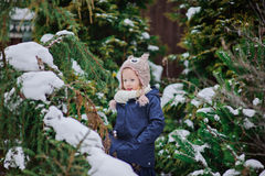 Happy child girl plays in winter snowy garden Royalty Free Stock Photos