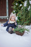 Happy child girl plays in winter snowy garden Stock Photo