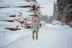 Happy child girl plays on winter snowy road with tree felling on background Stock Photography