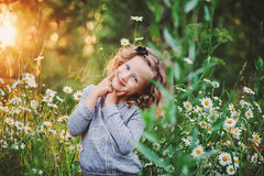 Happy child girl portrait on summer sunset field with flowers Royalty Free Stock Image