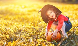Child girl with pumpkin outdoors in halloween Royalty Free Stock Photography