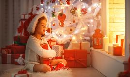 Happy child girl read book at christmas near   fireplace at home Royalty Free Stock Images