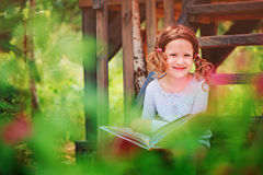 Happy child girl reading book outdoor Stock Photo
