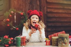 Happy child girl in red hat and scarf wrapping Christmas gifts at cozy country house, decorated for New Year and Christmas royalty free stock images