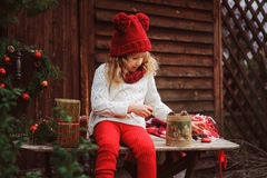 Happy child girl in red hat and scarf wrapping Christmas gifts at cozy country house, decorated for New Year and Christmas. Royalty Free Stock Photography