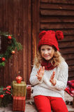 Happy child girl in red hat and scarf wrapping Christmas gifts at cozy country house, decorated for New Year and Christmas. Royalty Free Stock Photos