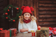 Happy child girl in red hat and scarf wrapping Christmas gifts at cozy country house, decorated for New Year and Christmas. Stock Image