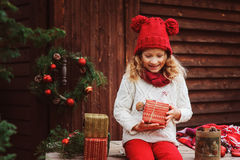 Happy child girl in red hat and scarf wrapping Christmas gifts at cozy country house, decorated for New Year and Christmas. Stock Photography