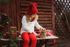 Happy child girl in red hat and scarf wrapping Christmas gifts at cozy country house, decorated for New Year and Christmas. Royalty Free Stock Image