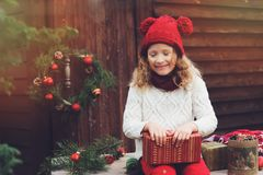 Happy child girl in red hat and scarf wrapping Christmas gifts at cozy country house, decorated for New Year and Christmas Stock Photos