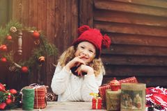 Happy child girl in red hat and scarf wrapping Christmas gifts at cozy country house, decorated for New Year and Christmas Stock Image