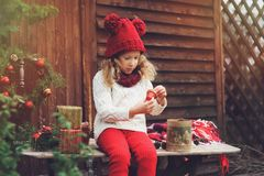Happy child girl in red hat and scarf wrapping Christmas gifts at cozy country house, decorated for New Year and Christmas Royalty Free Stock Image