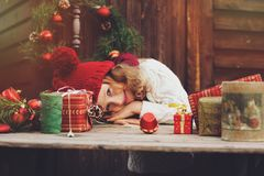 Happy child girl in red hat and scarf wrapping Christmas gifts at cozy country house, decorated for New Year and Christmas stock images