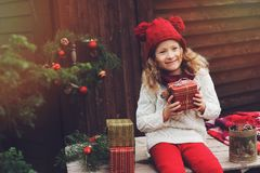 Happy child girl in red hat and scarf wrapping Christmas gifts at cozy country house, decorated for New Year and Christmas Royalty Free Stock Photos