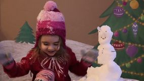 Girl sculpts a snowman in winter. Emotional portrait of cute little girl in winter. background of a painted Christmas stock video
