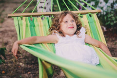 Happy child girl relaxing in hammock on summer camp in forest. Outdoor seasonal activities Stock Image