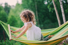 Happy child girl relaxing in hammock on summer camp in forest. Outdoor seasonal activities. For kids stock photo