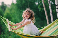 Happy child girl relaxing in hammock on summer camp in forest. Outdoor seasonal activities. For kids stock image