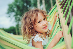 Happy child girl relaxing in hammock on summer camp in forest. Outdoor seasonal activities Stock Photo