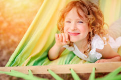Happy child girl relaxing in hammock in summer Stock Images