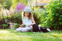 Happy child girl relaxing in summer garden with her spaniel dog, wearing gardener hat and holding bouquet of flowers Stock Images