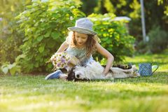 Happy child girl relaxing in summer garden with her spaniel dog, wearing gardener hat and holding bouquet of flowers Royalty Free Stock Photography