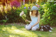 Happy child girl relaxing in summer garden with her spaniel dog, wearing gardener hat and holding bouquet. Of flowers. Blooming perennials on background Royalty Free Stock Image
