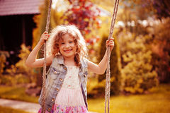 Happy child girl relaxing on swing in spring garden Royalty Free Stock Photos