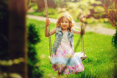 Happy child girl relaxing on swing in spring garden Stock Image