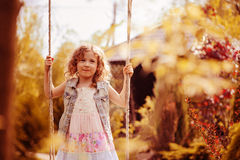 Happy child girl relaxing on swing in spring garden Stock Images