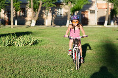 Happy child girl riding bicycle in summer sunset Stock Photography