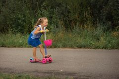 Happy child girl riding a scooter in the summer on the road stock images