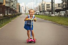 Happy child girl riding a scooter in the summer on the road stock photo
