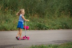 Happy child girl riding a scooter in the summer on the road royalty free stock images
