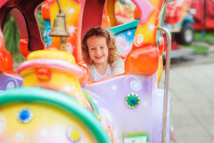 Happy child girl riding train on funfair on summer vacation Stock Images