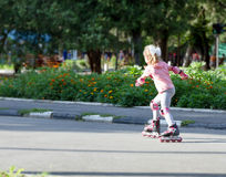 Happy child girl roller skating Royalty Free Stock Images