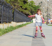 Happy child girl roller skating on natural background Stock Image