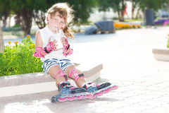 Happy child girl roller skating on natural background Stock Photography