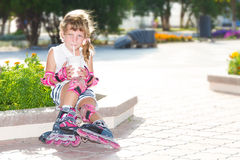 Happy child girl roller skating on natural background Stock Photo