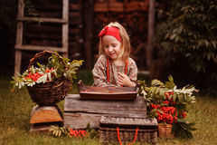 Happy child girl with rowan berries and decorations in autumn garden Royalty Free Stock Photography