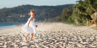 Happy child girl running on beach by sea in summer Royalty Free Stock Photography