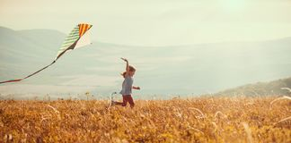 Happy child girl running with kite at sunset outdoors royalty free stock image