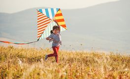 Happy child girl running with kite at sunset outdoors stock images