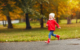 Happy child girl running in nature in autumn after rain Royalty Free Stock Photo