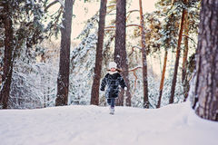 Happy child girl running on the walk in sunny winter forest Stock Image