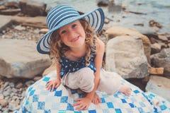 Happy child girl at sea, cozy summer holidays on seaside Stock Photos
