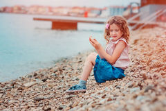Happy child girl on seaside on summer vacation in Piran, Slovenia, with city view on background Stock Photo